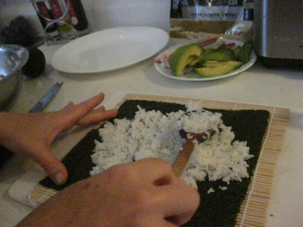 spreading rice on the sushi nori
